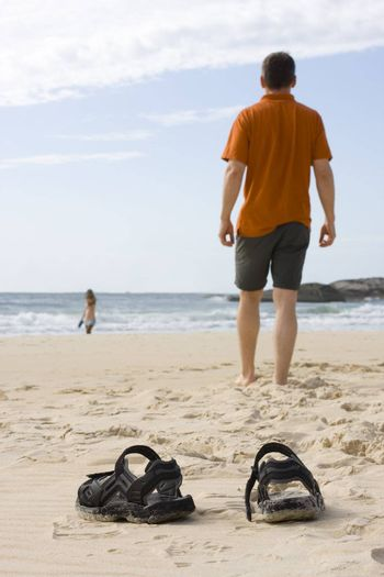 Man walking barefoot on a beach. Woman in the background. Focus on the sandals in the foreground.