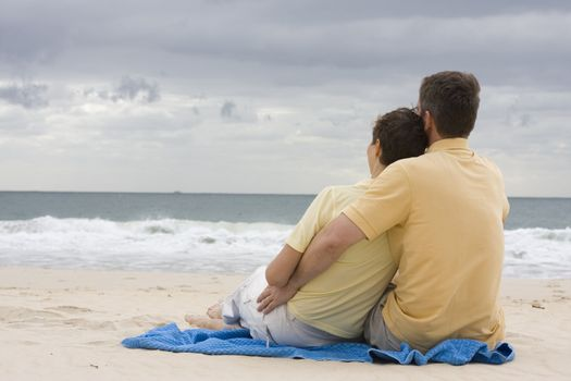 Attractive couple couple sitting on a blue towel on the beach