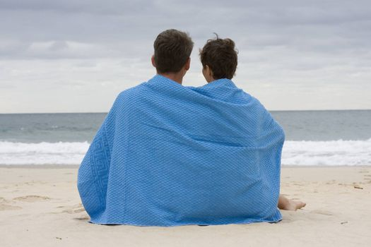 Couple sitting on the beach with a blue towel.