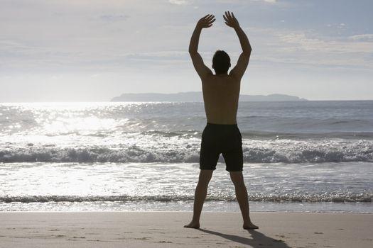 Man doing yoga on the beach at sunrise