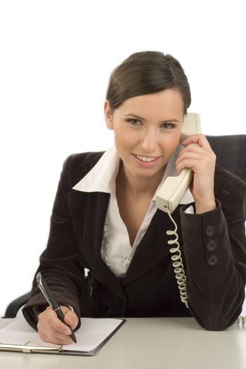 Young smiling businesswoman with telephone taking notes