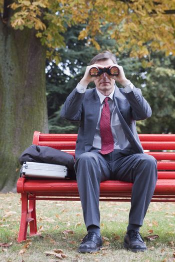 Businessman on a red park bench searching with binoculars