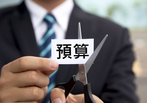 businessman with scissors cutting label chinese Budget
