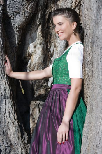 Bavarian woman in costume stands in a tree
