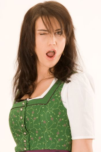 Emotional young Bavarian woman winking with one eye