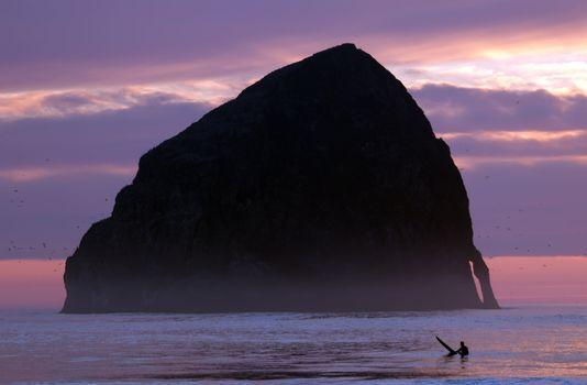Lonely surfer at dusk time in ocean at Oregon Cape Kiwanda