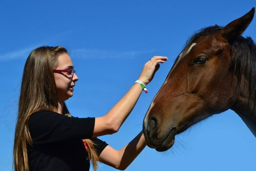 A long haired young woman caressing a brown horse with the sky in the background.