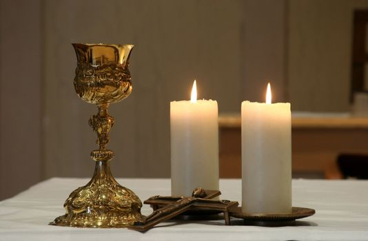 Golden chalice and two burning candles