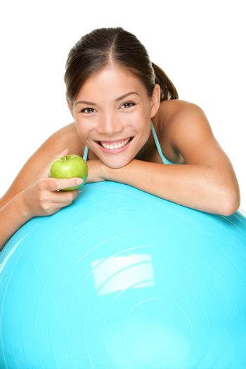 Sport fitness woman on exercise pilates ball eating an apple relaxing taking a break. Smiling happy multiracial female fitness model isolated on white background