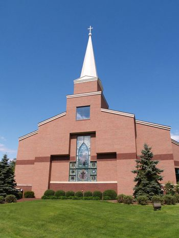 The front of a modern red brick church with a stained glass window.