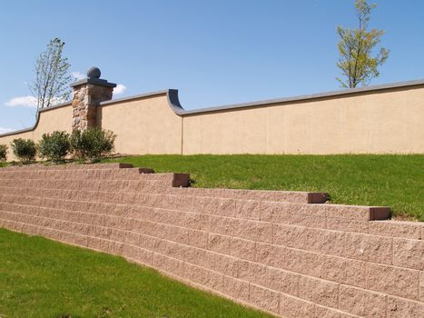 a brick retaining wall by a landscaped yard