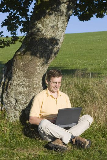 Man typing on a laptop while sitting in a meadow