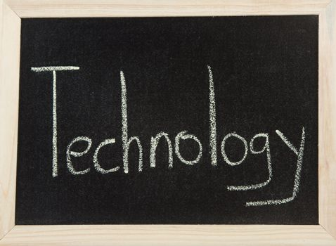 A black board with a wooden frame and the word 'TECHNOLOGY' written in chalk.