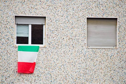 Italian flag on window with balcony in foreground