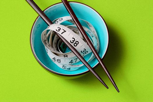 A light blue bowl on Green Background with a tape measure and chopsticks