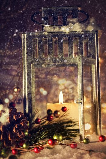 Brightly lit lantern with candle in the snow