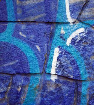 blue grafitti on stone wall