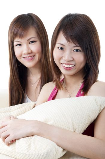 Two girls sitting on sofa, looking at camera.