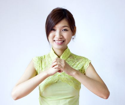 Oriental girl with traditional Cheongsam suit wishing you a happy Chinese New Year