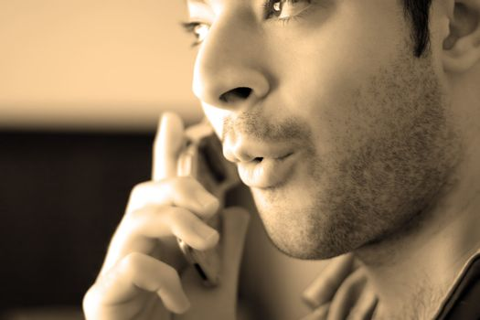 Sepia toned portrait of a young man on his celly phone - he looks surprised from what he has just heard.