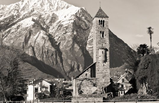 Sepia toned shot of an ancient Italian church with the Alps in the background