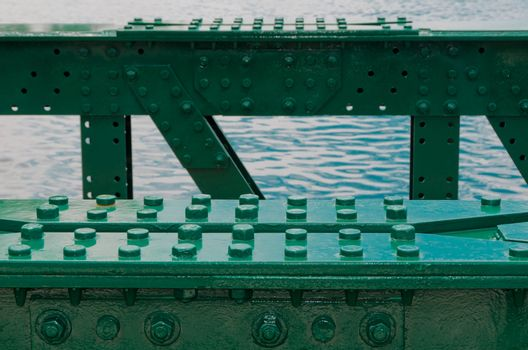 Construction of old green bridge, with lots of bolts and screws. Sea in background