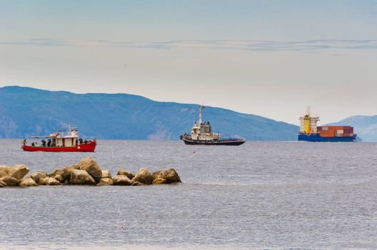 Three colorful ships near harbour of RIjeka during semi cloudy day