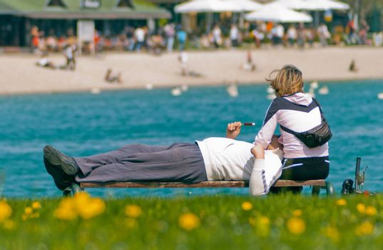 couple spending leisure time on a bench near lake