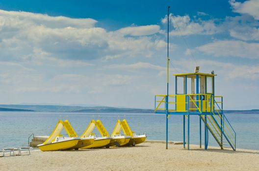yellow pedal boats near guard tower, on the beach