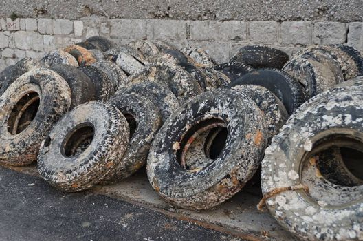 wasted tyres layed on the wall in a harbour