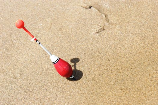 a fishing float sticked into the sand