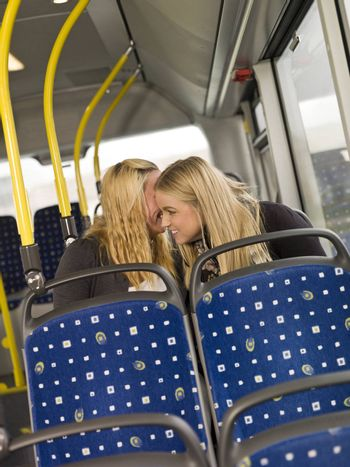 Two young women wispering secrets on the busn