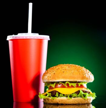 Tasty and appetizing hamburger on a darkly green background