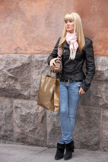 Young woman leaning to wall, holding shopping bag