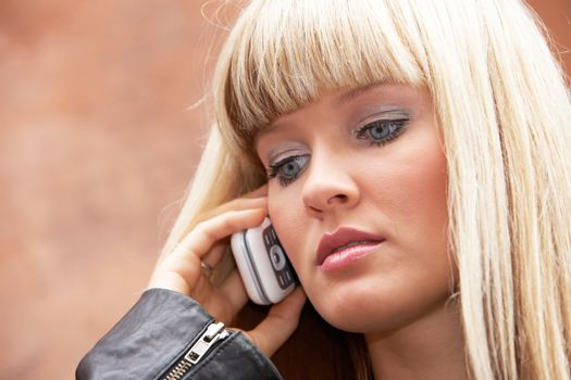 Close-up of young woman using mobile phone, looking down