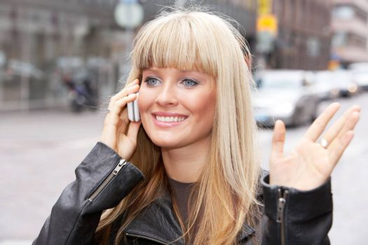 Young woman with mobile phone in street, waving