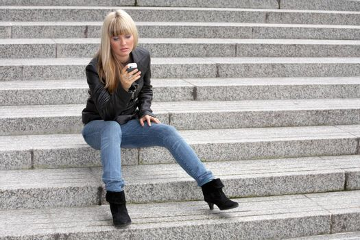 Young woman looking at mobile phone, sitting on stairway