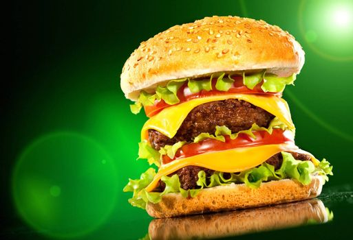 Tasty hamburger and french fries on a dark background