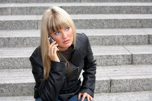 Young woman using mobile phone, looking away