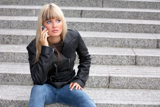 Young woman on mobile phone, looking away, sitting on stairway