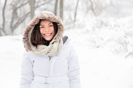 Snow winter woman portrait outdoors on snowy white winter day. Beautiful asian girl smiling happy outside.