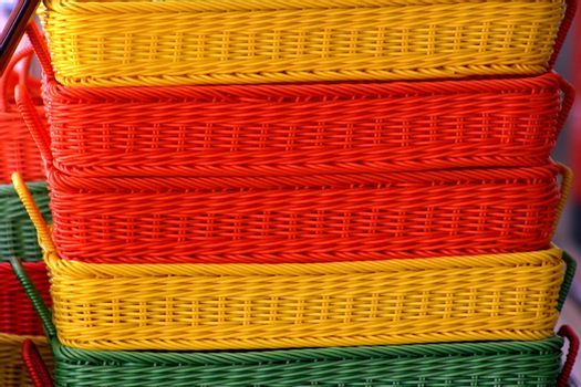 Stack of orange yellow and green baskets at a market place