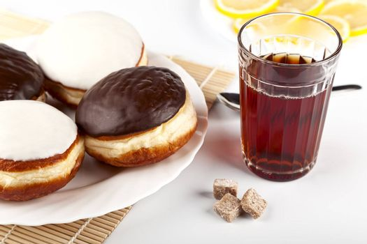 A cup of hot black tea and a plate of donuts