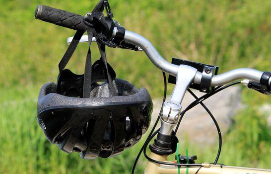 Bike helmet hanging on bicycle handle bar