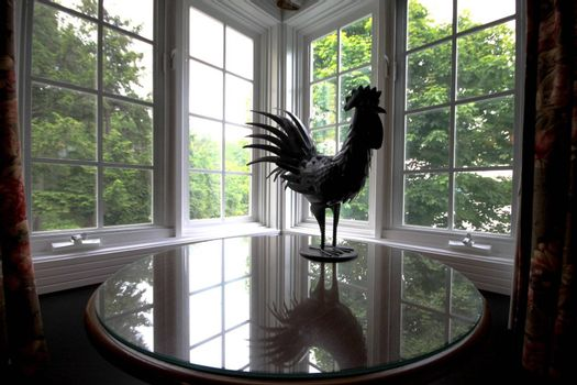 Metallic rooster reflected on a glass table in rustic surrounding