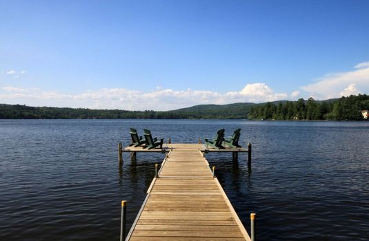 Lake side deck with chairs and summer sunshine