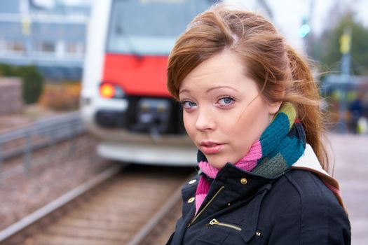 Teenage girl at railway platform, looking at camera