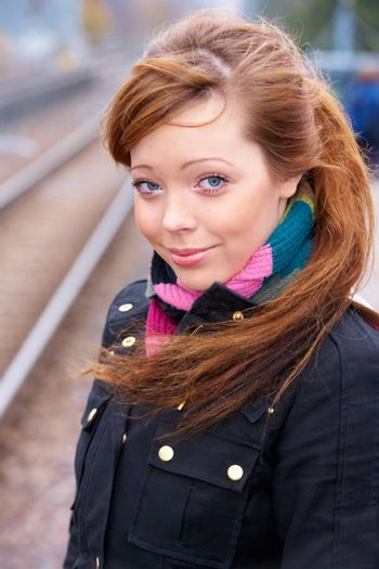 Teenage girl at railway platform, looking at camera, smiling