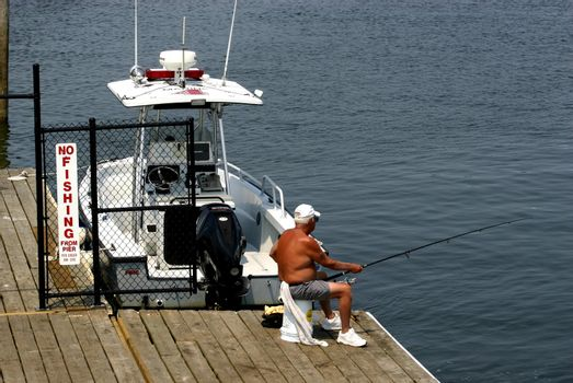 Man fishing on pier next to NO FISHING sign