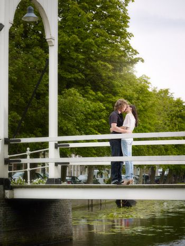 Boyfriend and girlfriend kissing on bridge